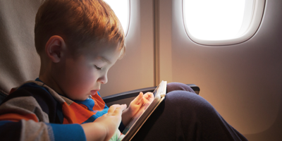 Child watching TV on a tablet in an airplane seat