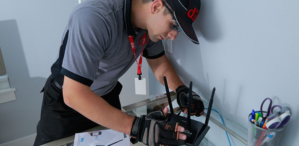 DISH Technician connecting cables on a wireless router