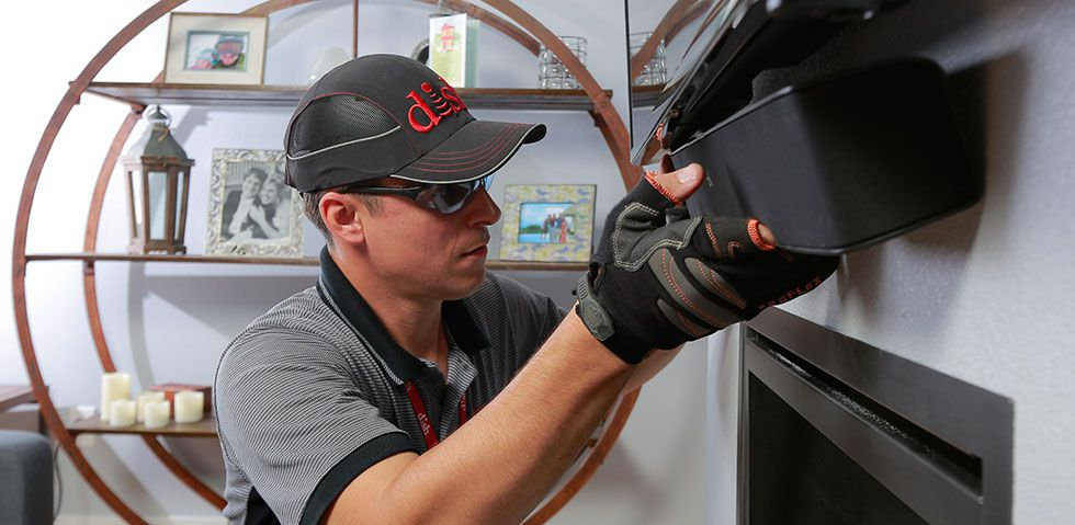 DISH Technician installing a Polk Audio soundbar below a wall-mounted TV
