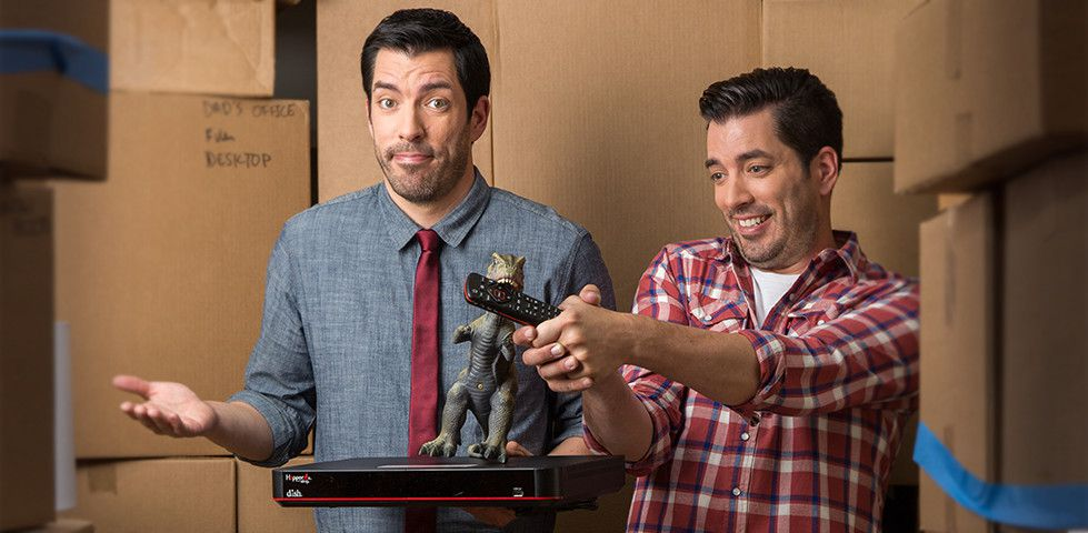 The Property Brothers holding a DISH Hopper receiver in a moving truck