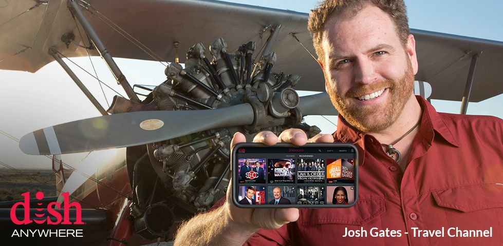 Josh Gates from Travel Channel, holding a phone with DISH Anywhere