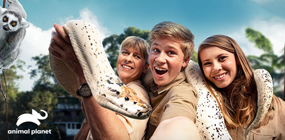 Terry, Bindi, and Robert Irwin surrounded by animals
