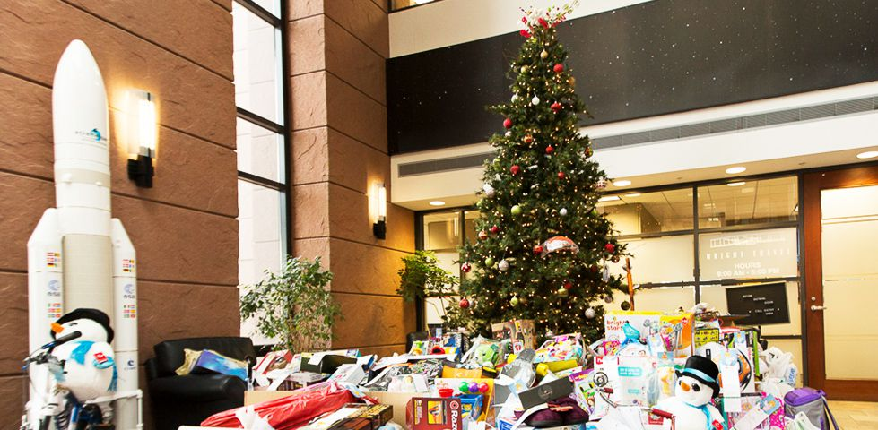 Piles of toys under a Christmas tree at DISH Headquarters