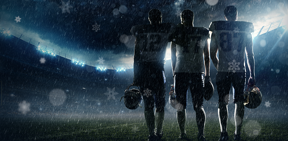 Three football players standing side by side in the rain