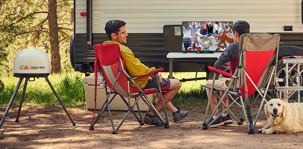 People watching TV while camping next to their RV