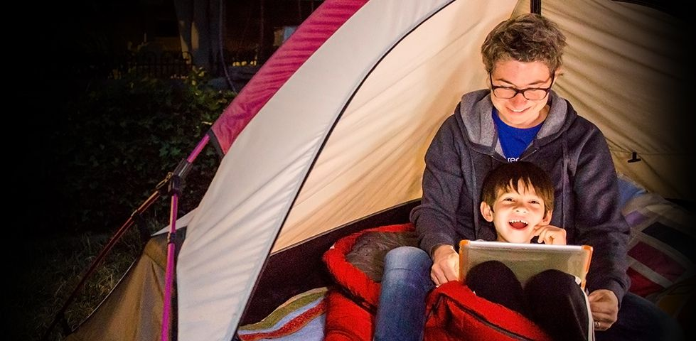 kids watching TV on a tablet in their tent