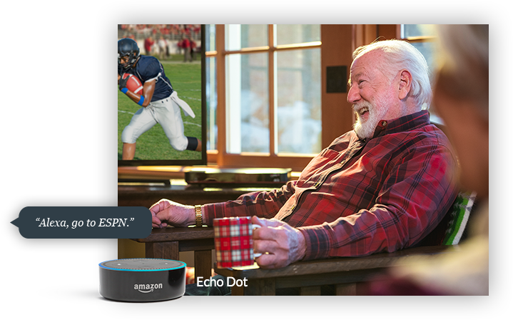 Man watching football, with an Amazon Echo Dot receiving the command 'Alexa, go to ESPN'
