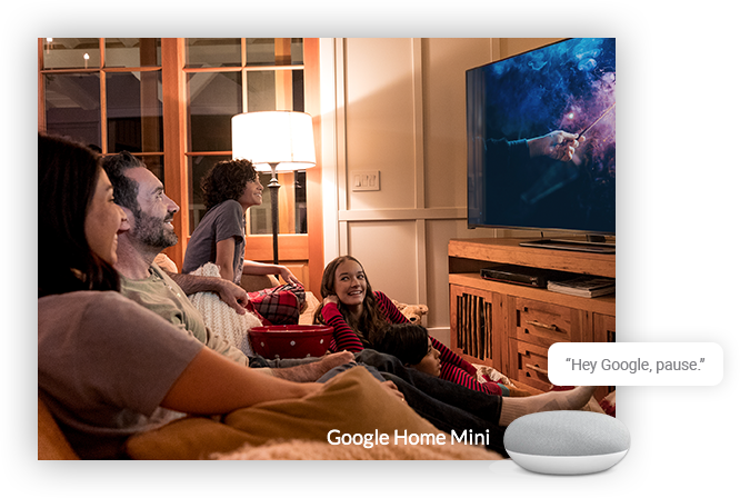 Family watching TV, with a Google Home Mini receiving the command 'Hey Google, pause'