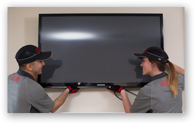 technicians mounting a TV to the wall