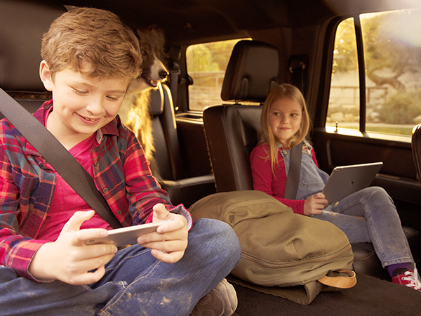Children watching TV on their tablet and phone in the backseat of a van